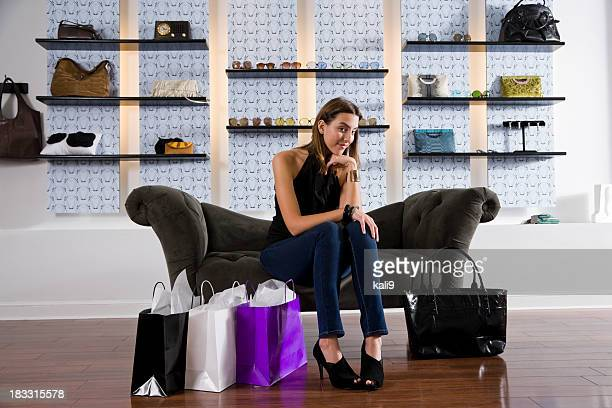 Young woman in boutique relaxing on sofa with shopping bags