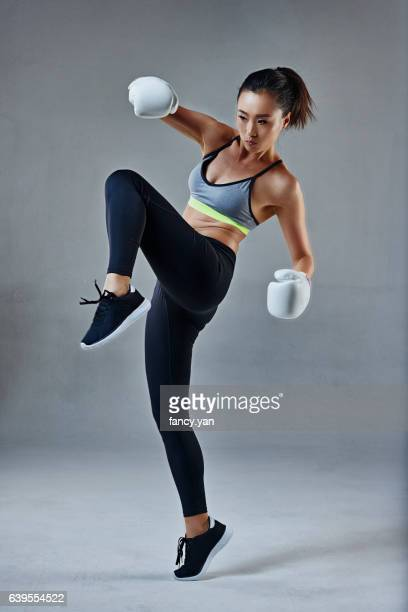 young woman in boxing gloves kicking - boxing sport stock pictures, royalty-free photos & images