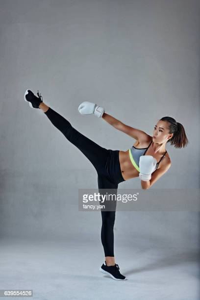 Young woman in boxing gloves kicking