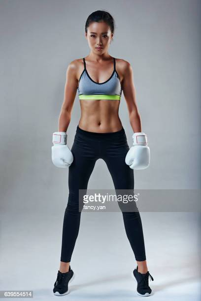 young woman in boxing gloves - asian female bodybuilder stock photos and pictures