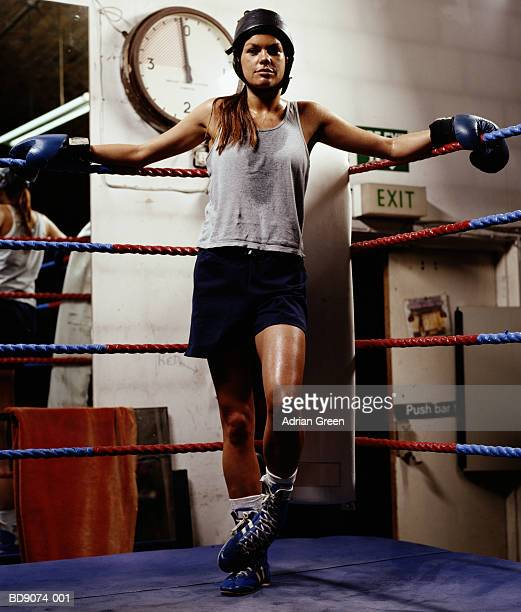 young woman in boxing ring, leaning on ropes - women's boxing stock pictures, royalty-free photos & images
