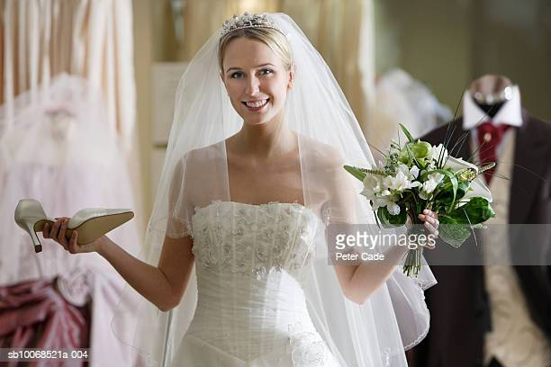 Young woman in bridal shop, wearing wedding dress, holding flowers and shoe, smiling