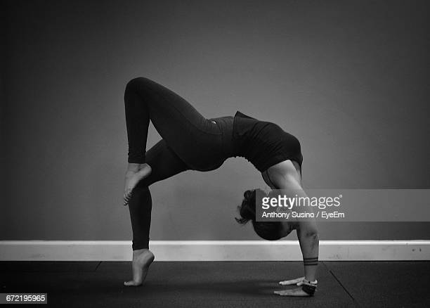 Young Woman In Bridge Pose Against Wall