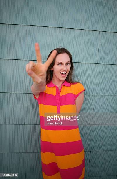 Young woman in bright colors giving peace sign