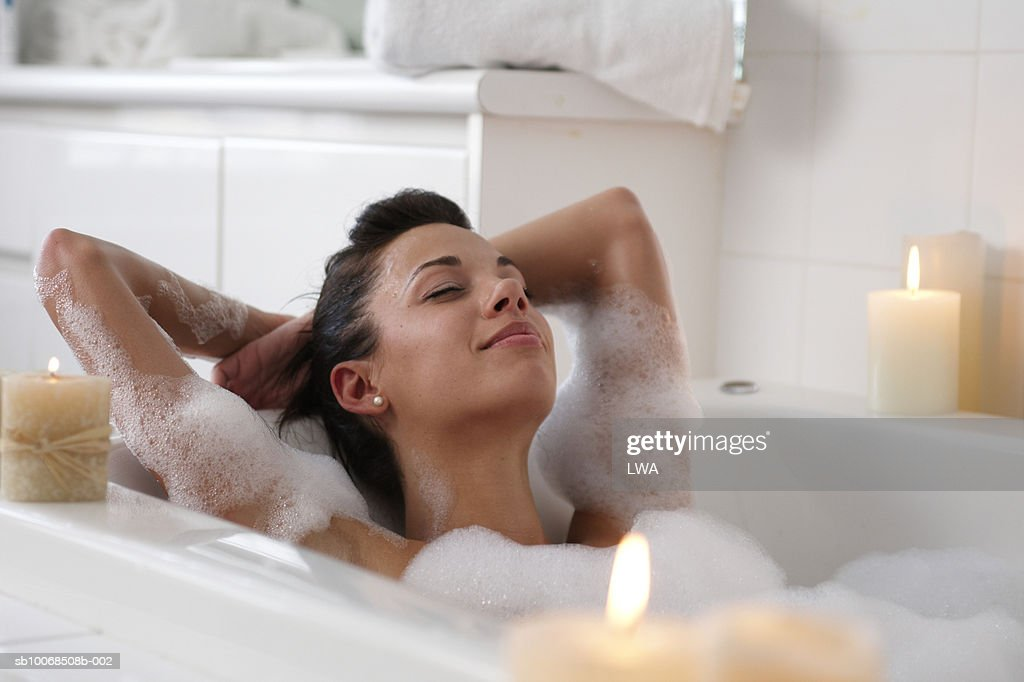 Young woman in bubble bath, smiling : Stock Photo