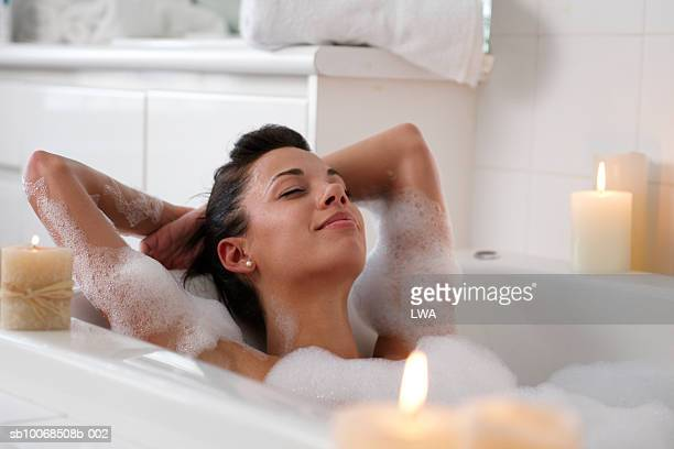 young woman in bubble bath, smiling - body care stock pictures, royalty-free photos & images