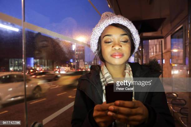 young woman in bus stop at night on phone - searching stock pictures, royalty-free photos & images