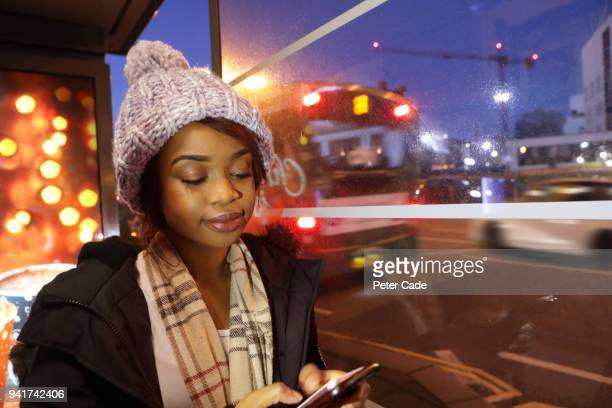 Young woman in bus stop at night on phone