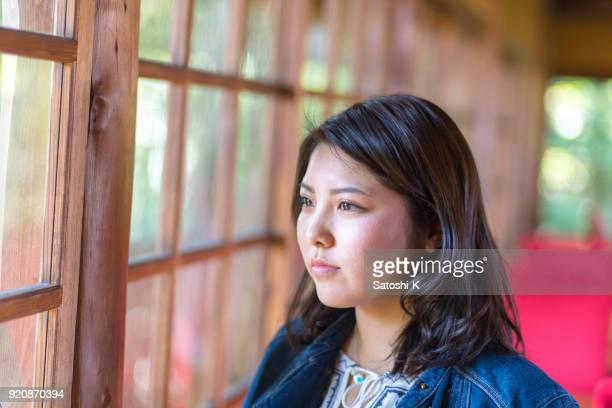 窓の外をカフェの若い女性