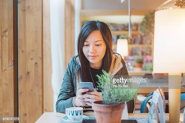 young woman in cafe smiling and texting on phone - yiu yu hoi stock pictures, royalty-free photos & images