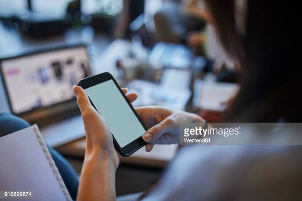 Young woman in cafe using smartphone with laptop in background