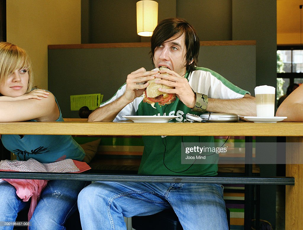 Young woman in cafe watching man bite into sandwich : Stock-Foto