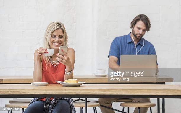 Young woman in cafe with cell phone drinking coffee