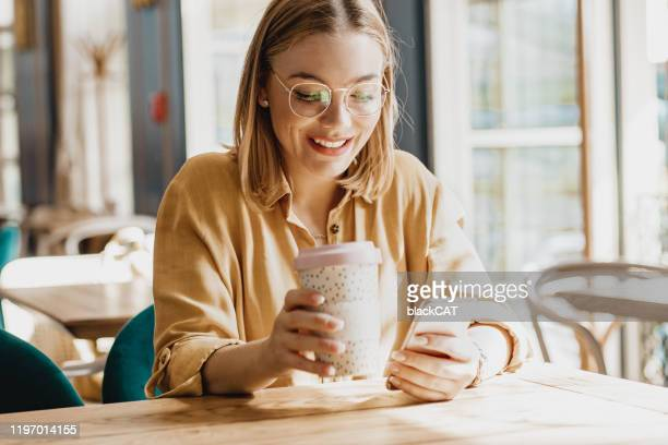 young woman in cafeteria using phone - reusable stock pictures, royalty-free photos & images