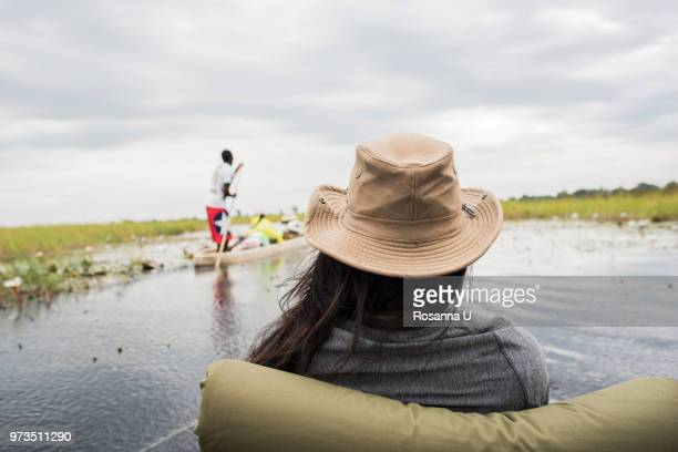 Young woman in canoe on Okavango Delta, rear view, Botswana, Africa
