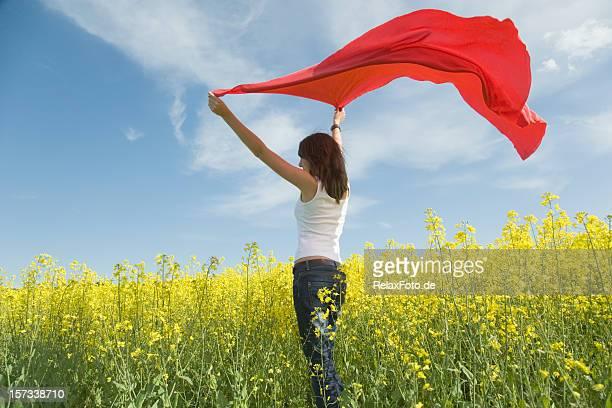 Young woman in キャノーラフィールドを保持赤のスカーフ風