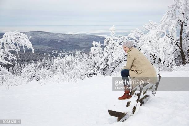 Young woman in cap and jacket sitting on fence in snow