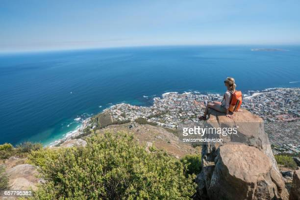young woman in cape town on top of mountain looking at view - table mountain stock pictures, royalty-free photos & images