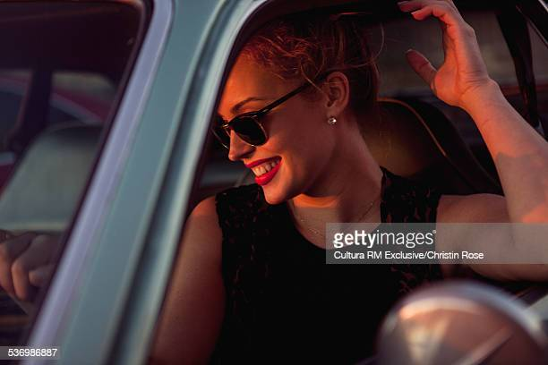 Young woman in car, laughing