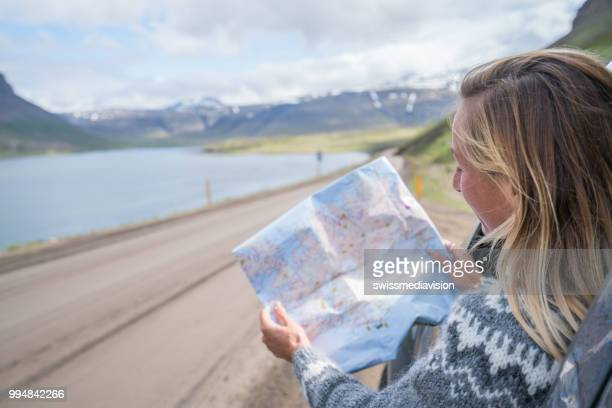 young woman in car looking at map, road trip concept vacations - vehicle interior stock pictures, royalty-free photos & images