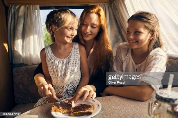young woman in caravan preparing a toast with chocolate spread for her sister - nutella stock pictures, royalty-free photos & images