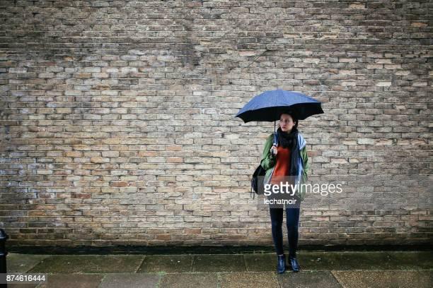 junge frau im zentrum von london, hält einen regenschirm - regenschirm stock-fotos und bilder