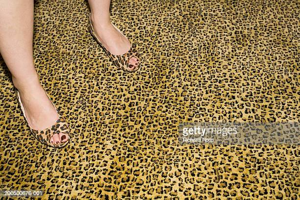 young woman in cheetah-print shoes standing on cheetah-print carpet - kitsch stock pictures, royalty-free photos & images