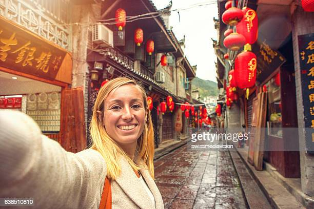 young woman in chinese street taking selfie portrait - niet westers schrift stockfoto's en -beelden