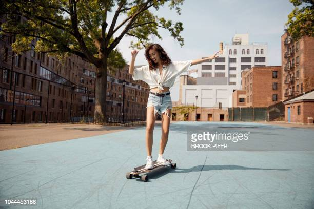young woman in city on skateboard - denim shorts stock pictures, royalty-free photos & images
