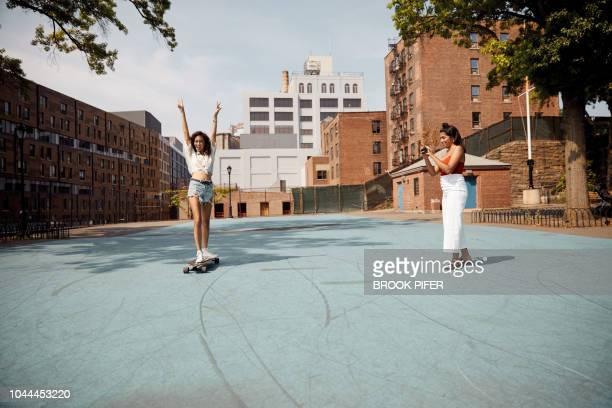young woman in city on skateboard - temi per la fotografia foto e immagini stock