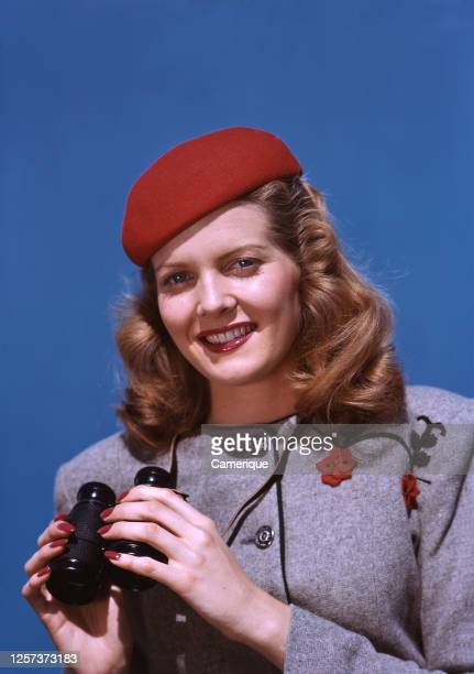 Young woman in classy grey suit and red hat standing with binoculars