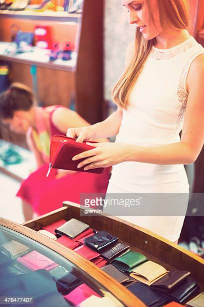Young woman in clothing store checking new purse