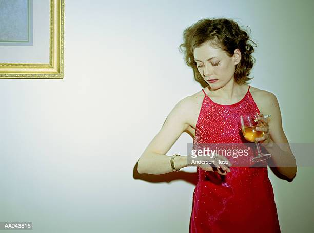 Young woman in cocktail dress looking at watch