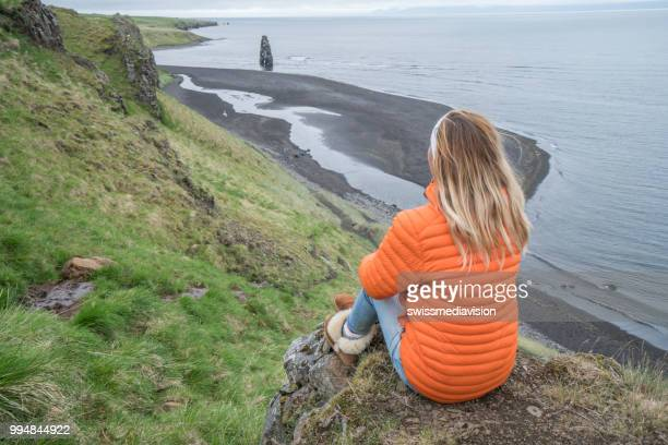 Young woman in contemplating Hvitserkur basalt stack along the eastern shore of the Vatnsnes peninsula, in northwest Iceland