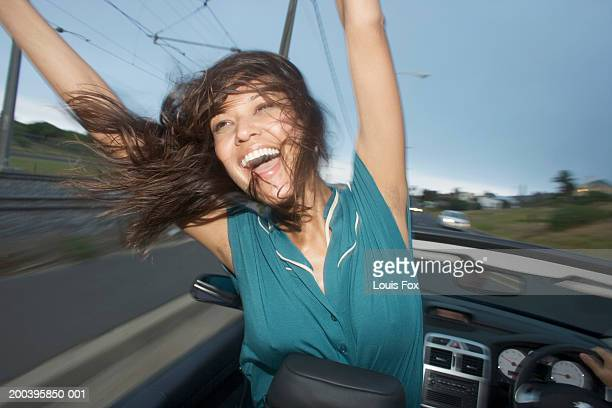 young woman in convertible car, arms raised, smiling - open blouse stock photos and pictures