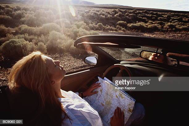 Young woman in convertible car, holding map