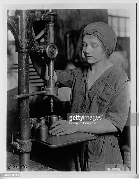 A young woman in coveralls uses an electic drill to retap the base of a grenade's detonater tube Pittsburgh
