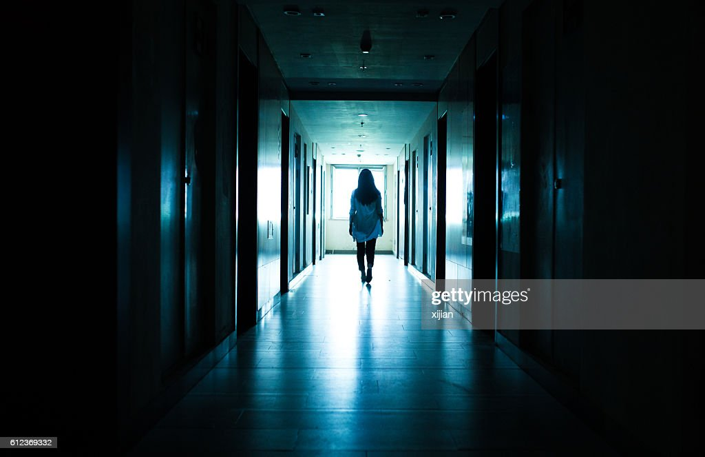Young woman  in dark building walkway : Foto de stock