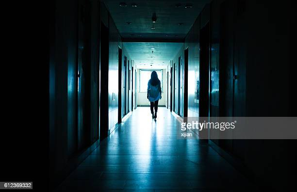 young woman  in dark building walkway - violenza foto e immagini stock