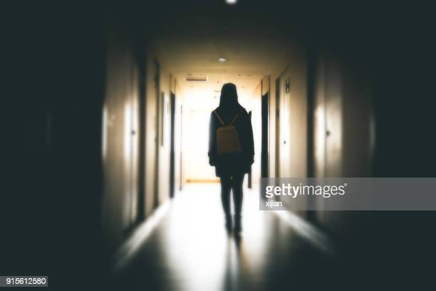 young woman in dark building walkway - fear stock pictures, royalty-free photos & images