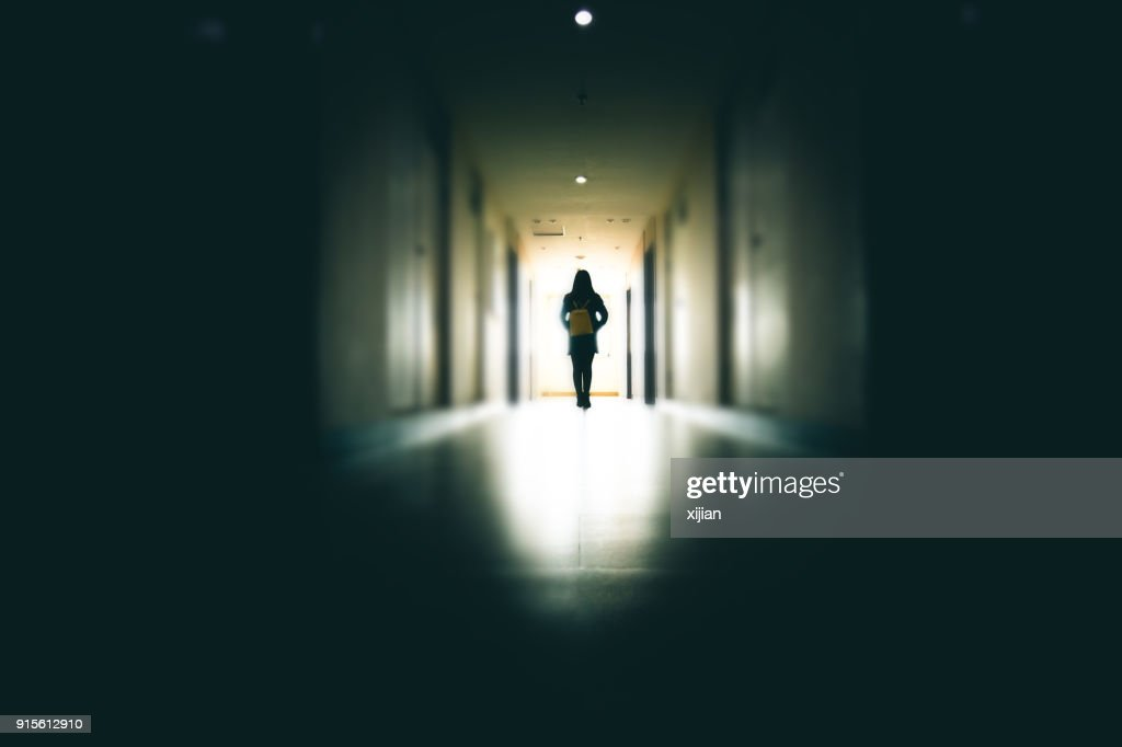 Young woman in dark building walkway : Foto stock