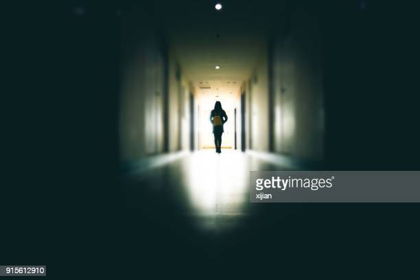 young woman in dark building walkway - harassment stock photos and pictures
