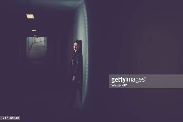 young woman in dark underpass - ominous stock photos and pictures