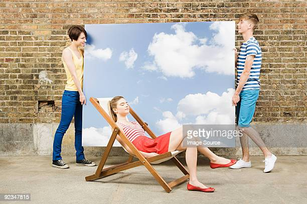 young woman in deckchair and others with sky backdrop - girls sunbathing stock pictures, royalty-free photos & images