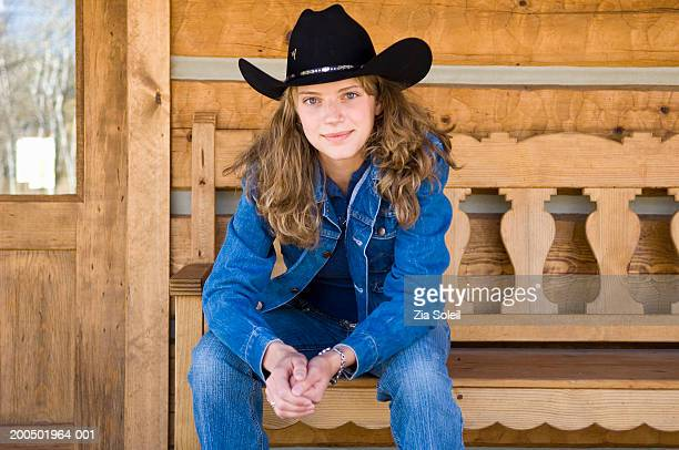 Young woman in denim and cowboy hat sitting on veranda bench, portrait