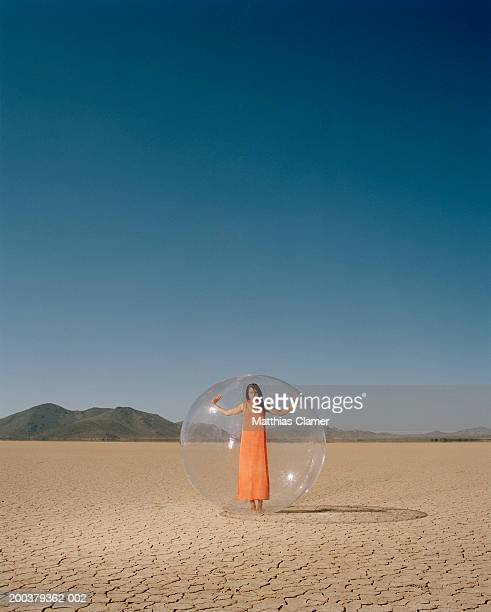 Young woman in desert standing in plastic bubble, portrait