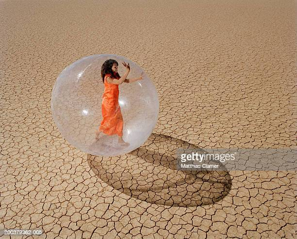 Young woman in desert walking in plastic bubble, side view