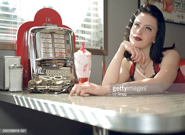 Young woman in diner, resting chin on hand, looking upwards