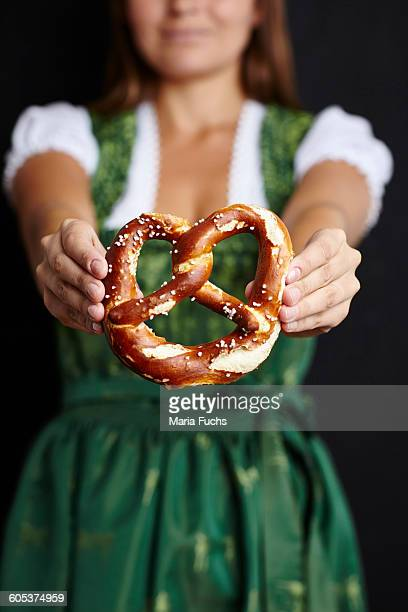 Young woman in Dirndl holding pretzel