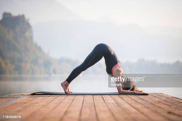 young woman in dolphin pose on pier overlooking lake bled - inclinar se pose imagens e fotografias de stock